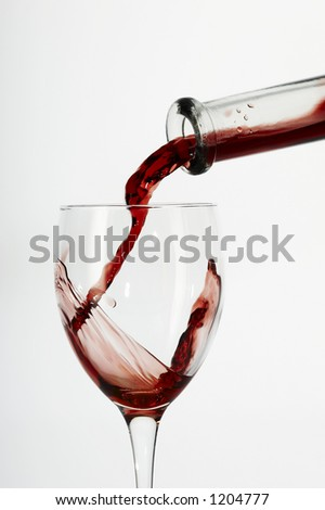 Flowing red wine from bottle to glass