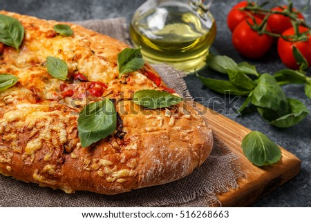 Focaccia with tomatoes, herbs and cheese, garnished with basil leaves.