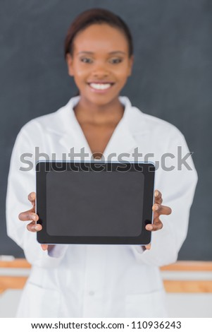 Focus on a black woman holding a tablet computer in a classroom