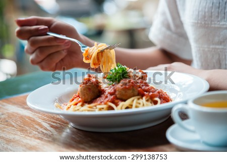 focus on woman eating spaghetti with cup of tea
