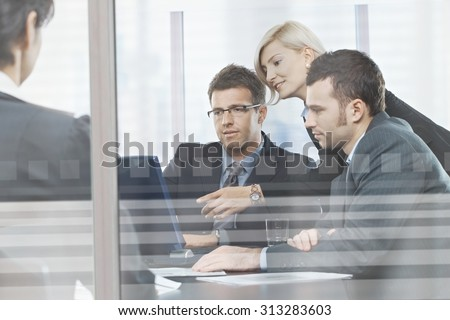 Focused caucasian business people meeting in boardroom behind glass. Sitting at table, wearing suit, looking at screen, pointing.