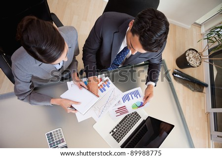 Focused sales persons studying statistics in an office