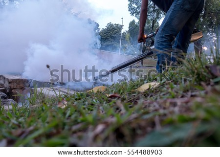 Fogging into the drain to prevent spread of dengue fever - low angle