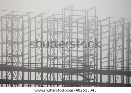 foggy morning. fog on the high-rise construction site frame building. constructions poorly visible in the fog