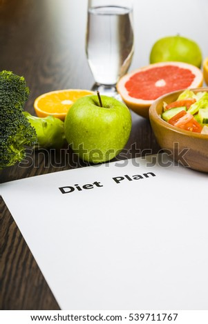 Food and sheet of paper with a diet plan on a dark wooden table. Concept of diet and healthy lifestyle.