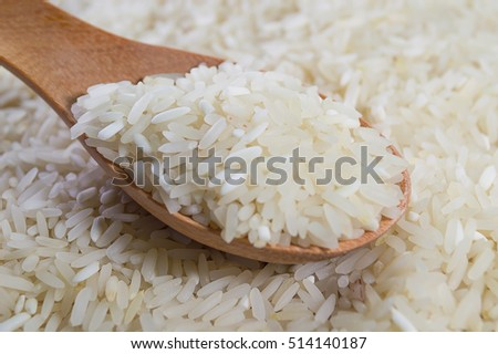 Food background. Jasmine rice in a wooden spoon.