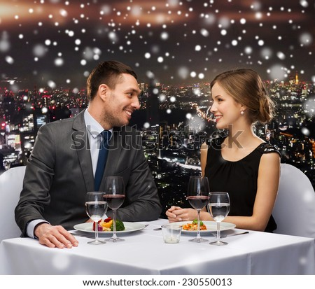 food, christmas, holidays and people concept - smiling couple eating main course at restaurant over snowy night city background