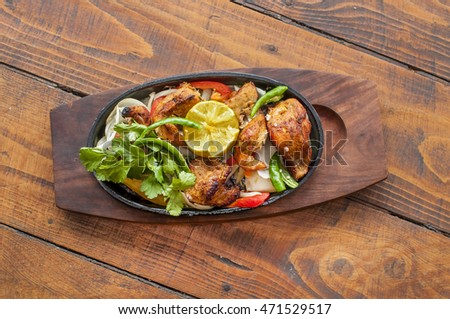 Food grilled chicken pieces on a wooden dish