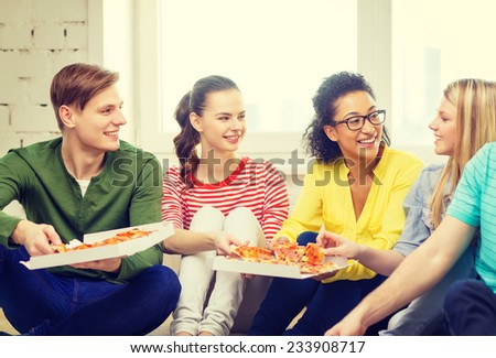 food, leisure and happiness concept - five smiling teenagers eating pizza at home