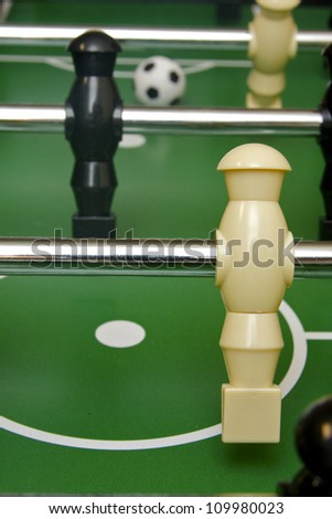 Foosball and soccer game table with ball in background