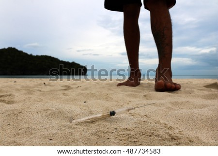 Foot walking with injection needles on the beach.
