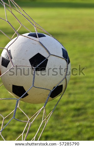Football is hitting the goal net in vertical shot