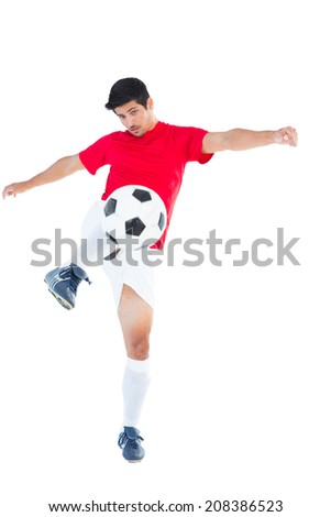 Football player in red kicking ball on white background