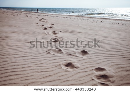 Footprints in the sand of the sea