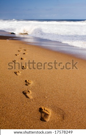Footprints on the beach sand, leading away from the viewer into the sea