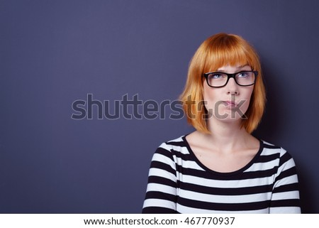 Forgetful young woman trying to remember something grimacing and frowning as she searches her memory, head and shoulders on blue with copy space