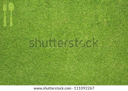 Fork and spoon icon on green grass texture and  background
