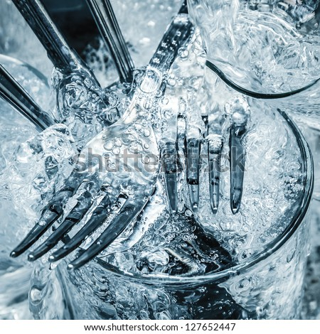 Forks,knives and glasses under a stream of water