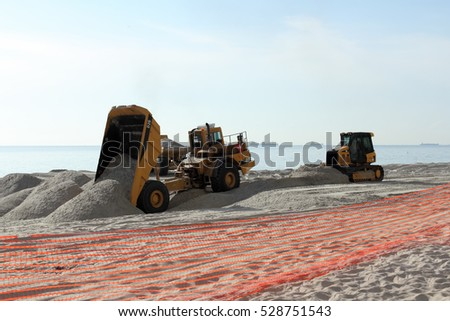 Fort Lauderdale, FL, USA - March 3, 2016: Two dump trucks and a bulldozer work on beach nourishment on the coast. Earth moving equipment add sand to a public beach.