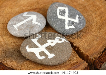 ... telling with symbols on stones on wooden background - stock photo