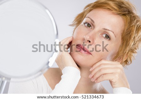 Forty years woman face and mirror