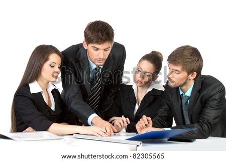 four attractive positive young business people in elegant suits sitting at desk working in team together and discussing the problem, business plan, papers, document, Isolated over white background