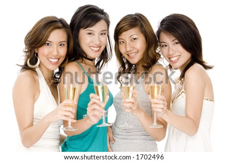 Four attractive young asian women drinking glasses of champagne