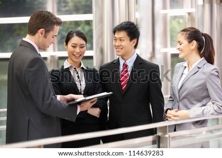 Four Business Colleagues Discussing Document Outside Office