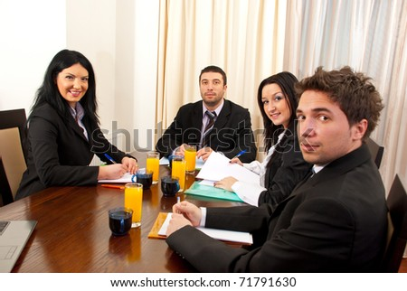 Four business people having a meeting and sitting at table with paperwork