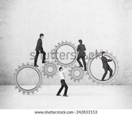 four businessman pushing metal wheel and gears