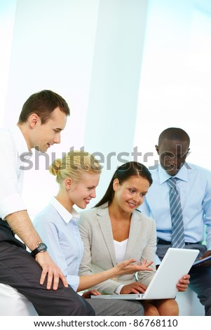 Four businesspeople in office looking at laptop and talking