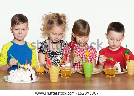Four cheerful children celebrate a birthday at the table