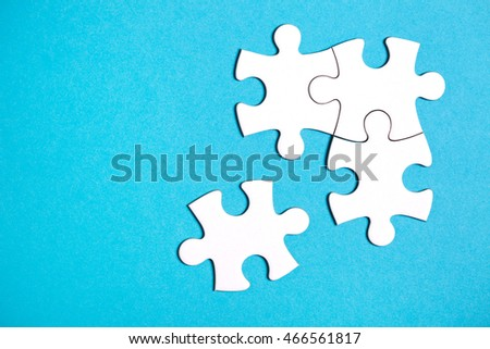 Four disconnected jigsaw puzzle pieces on blue background. The concept of finding the right solutions in teamwork.