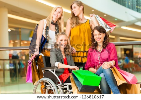 Four female friends with shopping bags having fun while shopping in a mall, stores in the background; one woman is sitting in a wheelchair