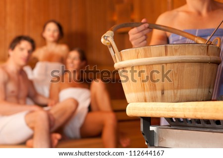 Four friends - three women, one man - doing wellness in the sauna of a thermal bath