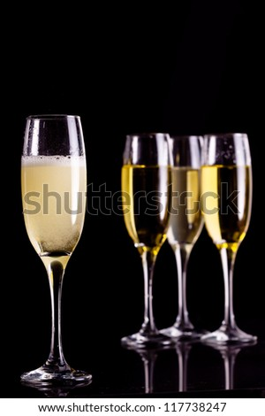 Four full flutes of champagne against black background