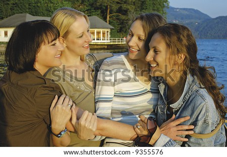 Four girls having fun beside a lake.