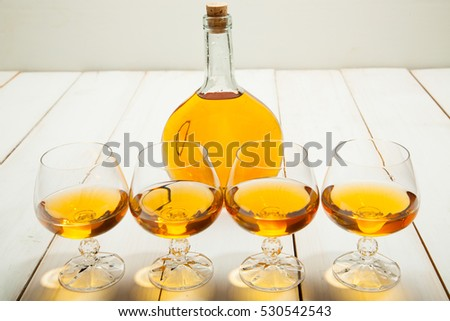 Four glasses of brandy and bottle on a white wooden table