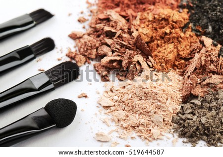 four makeup brushes and crumbled eyeshadow of different colors on a white background horizontal