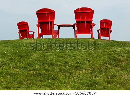 Four red Adirondack beach chairs on a grassy slope.