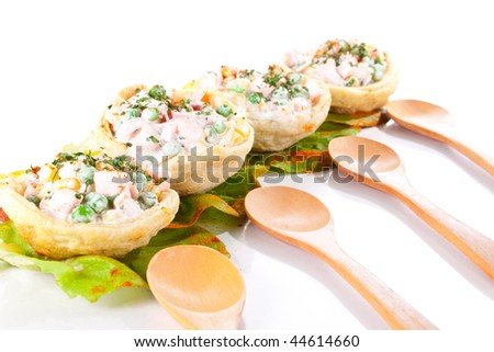 four russian salad in tortillas with wooden spoons