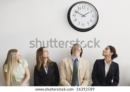 Four seated office workers looking at clock