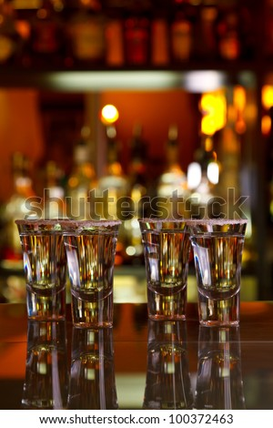 four shots of tequila with lime and salt on table bar, background light
