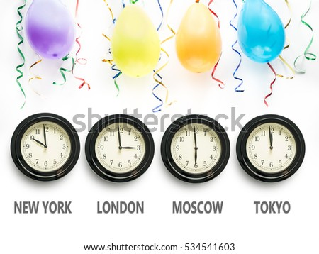 Four wall clocks indicating time zones for New York, London, Moscow and Tokyo with Tokyo time showing almost midnight and the New Year's Day. The wall decorated with balloons and streamers