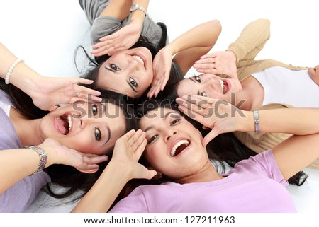 four young attractive asian women relaxing smiling lying on the floor