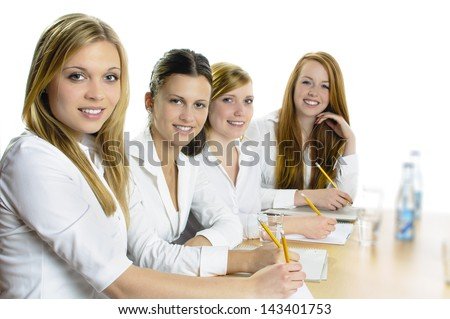 Four young women sitting at a table and hold a pencil in hand, they look happy in the camera, isolated against a white background.