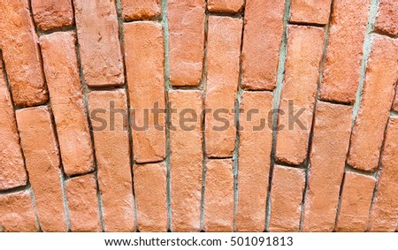 Fragment of a red brick wall with an arch.