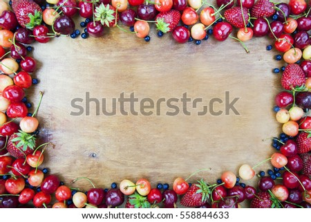 Frame from fruit for a card on the background of wooden boards