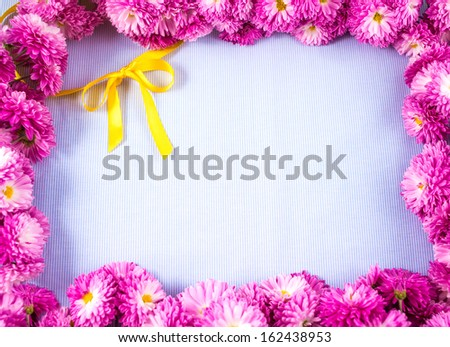 Frame of pink chrysanths on blue background