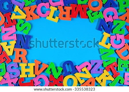 Frame of plastic colorful alphabet letters on a  blue background
